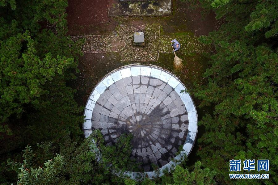 A drone photo shows Zhao Naitang, 73, working at the Huangyadong Martyrs Cemetery in Licheng County, North China's Shanxi Province, Sept. 20, 2018. Huangyadong used to be an arsenal of the Eighth Route Army and a battlefield during the Chinese People\'s War of Resistance against Japanese Aggression. Zhao has been the custodian at the cemetery, where 44 martyrs were buried, since 1991. (Photo/Xinhua)
