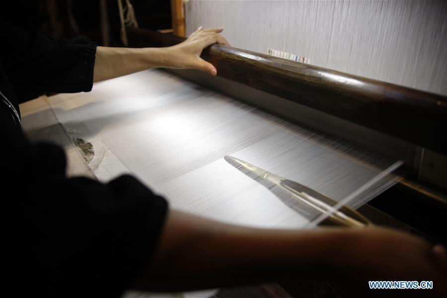 A weaver knits Yun brocade at the Nanjing Yunjin Museum in Nanjing, capital of east China\'s Jiangsu Province, Sept. 26, 2018. Yunjin, also called Yun brocade, is traditional Chinese silk brocade made in Nanjing of Jiangsu. Dated from the Eastern Jin Dynasty, it has formed its own characteristics through its development of 1,600 years. Yun brocade is famous for its exquisite craft, elegant patterns and smooth texture, and the making of the artwork requires close cooperation of two weavers, who can produce only five centimeters a day. In 2009, Yun brocade was inscribed on the Representative List of the Intangible Cultural Heritage of Humanity. (Xinhua/Zhu Weixi)