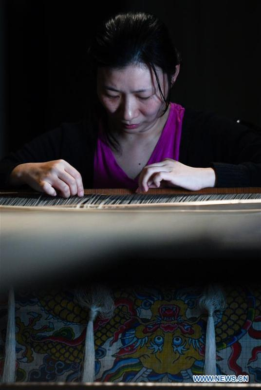 A weaver shows skills of knitting Yun brocade at the Nanjing Yunjin Museum in Nanjing, capital of east China\'s Jiangsu Province, Sept. 26, 2018. Yunjin, also called Yun brocade, is traditional Chinese silk brocade made in Nanjing of Jiangsu. Dated from the Eastern Jin Dynasty, it has formed its own characteristics through its development of 1,600 years. Yun brocade is famous for its exquisite craft, elegant patterns and smooth texture, and the making of the artwork requires close cooperation of two weavers, who can produce only five centimeters a day. In 2009, Yun brocade was inscribed on the Representative List of the Intangible Cultural Heritage of Humanity. (Xinhua/Li Xiang)
