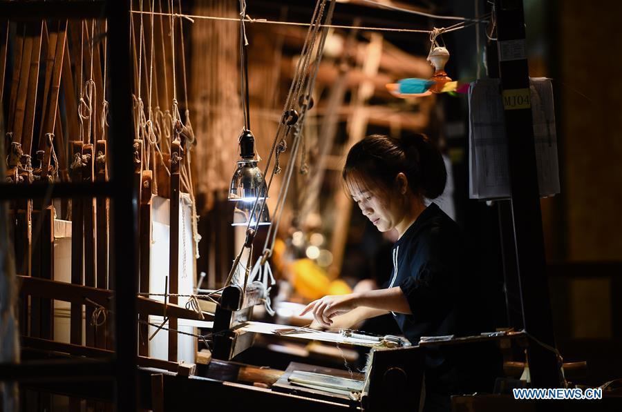 A weaver knits Yun brocade at the Nanjing Yunjin Museum in Nanjing, capital of east China\'s Jiangsu Province, Sept. 26, 2018. Yunjin, also called Yun brocade, is traditional Chinese silk brocade made in Nanjing of Jiangsu. Dated from the Eastern Jin Dynasty, it has formed its own characteristics through its development of 1,600 years. Yun brocade is famous for its exquisite craft, elegant patterns and smooth texture, and the making of the artwork requires close cooperation of two weavers, who can produce only five centimeters a day. In 2009, Yun brocade was inscribed on the Representative List of the Intangible Cultural Heritage of Humanity. (Xinhua/Li Xiang)