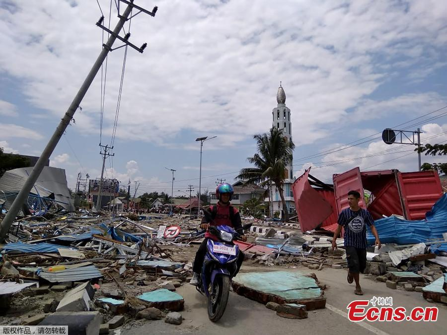 Residents make their way along a street full of debris after an earthquake and tsunami hit Palu, on Sulawesi island on September 29, 2018. Rescuers scrambled to reach tsunami-hit central Indonesia and assess the damage after a strong quake brought down several buildings and sent locals fleeing their homes for higher ground. (Photo/Agencies)