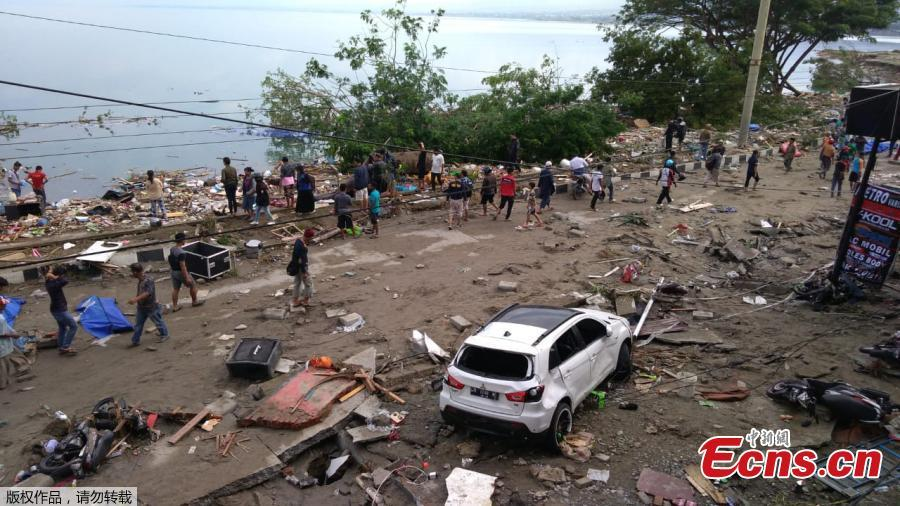 People walk past dead bodies (blue cover) a day after an earthquake and a tsunami hit Palu, on Sulawesi island on September 29, 2018. Rescuers scrambled to reach tsunami-hit central Indonesia and assess the damage after a strong quake brought down several buildings and sent locals fleeing their homes for higher ground.(Photo/Agencies)
