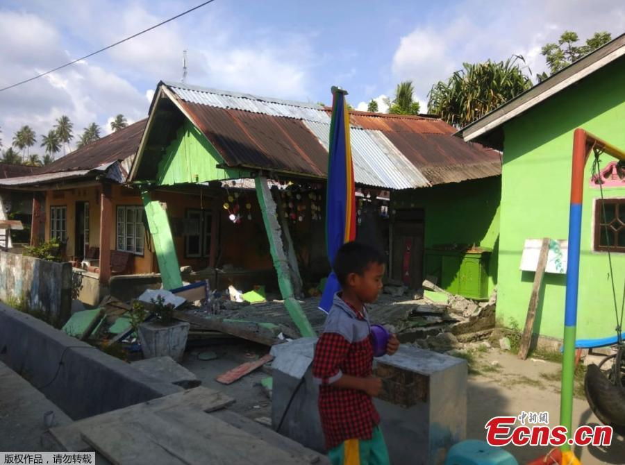 A handout photo made available by the Indonesian National Board for Disaster Management (BNPB) shows a boy walking in front of a collapsed house after an earthquake in Donggala, Central Sulawesi, Indonesia, Sept. 28, 2018. A tsunami caused deaths when it hit a small city on the Indonesian island of Sulawesi on Friday after a major quake, collapsing buildings and cutting off power, officials said, although the exact number of casualties was not clear.(Photo/Agencies)