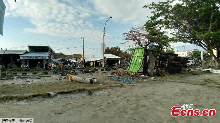 People look at the aftermath of the tsunami in Palu, on Sulawesi island on September 29, 2018. Rescuers scrambled to reach tsunami-hit central Indonesia and assess the damage after a strong quake brought down several buildings and sent locals fleeing their homes for higher ground.(Photo/Agencies)