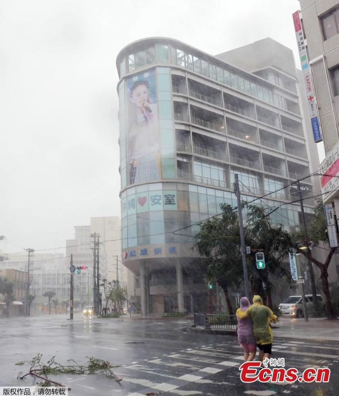 A couple crosses the street in the city center of Naha, Okinawa prefecture, Sept. 29, 2018 as the island is the first part of Japan to face the typhoon Trami. (Photo/Agencies)