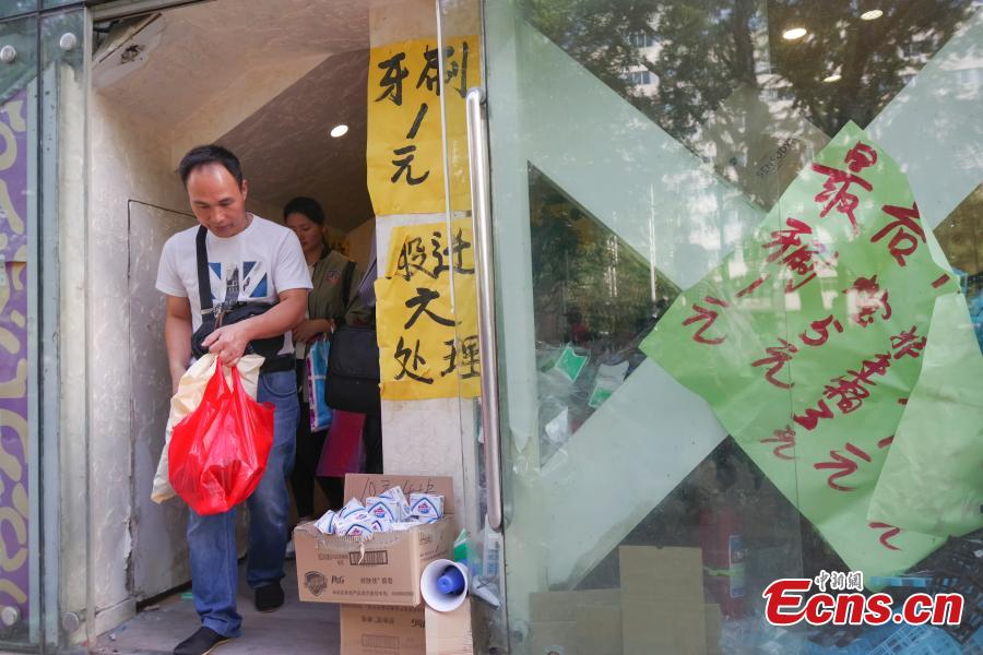 Customers purchase goods during a clearance sale at the Guanyuan Wholesale Market in Xicheng District, Beijing, Sept. 28, 2018. The market, opened in 1998, was shut down permanently on Friday as the capital continues efforts to remove non-capital functions and solve \
