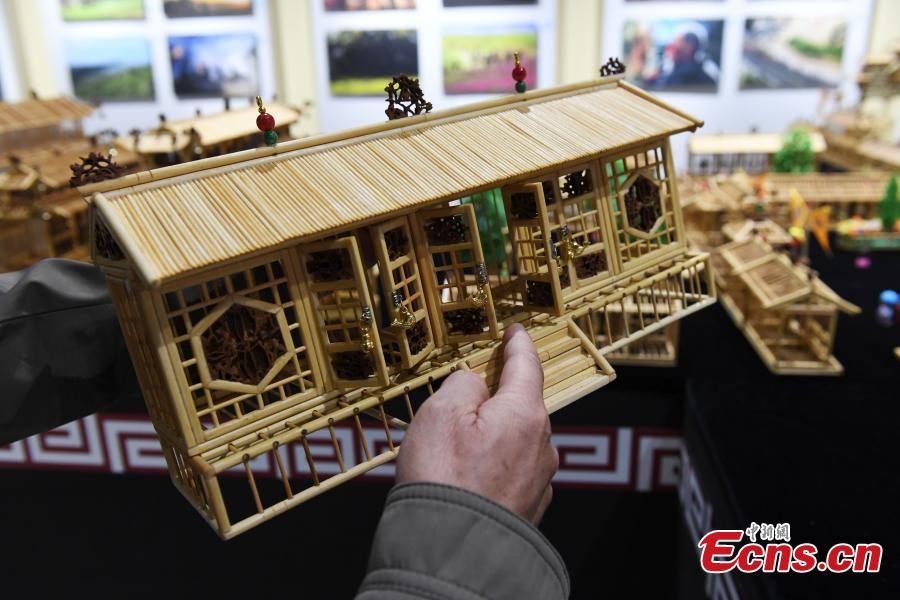Craftsman Wu Tianxiang shows a replica of Fuxi Temple in Tianshui City made using bamboo sticks during the Silk Road (Dunhuang) International Cultural Expo in Dunhuang City, Northwest China's Gansu Province, Sept. 28, 2018. It took Wu five years and 20,000 bamboo sticks to create the miniaturized landscape that measured 4.8 meters long and 4.2 meters wide and included 58 buildings in great details. Each door and window in the model can be opened easily. (Photo: China News Service/Yang Yanmin)