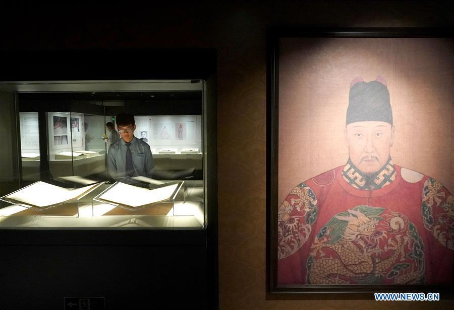 A staff member views exhibits during an exhibition on Yongle Encyclopaedia at National Library of China in Beijing, capital of China, Sept. 28, 2018. Yongle Encyclopaedia is China\'s first encyclopaedia compiled in the Ming Dynasty (1368-1644). The exhibition kicked off here on Friday. (Xinhua/Yin Gang)
