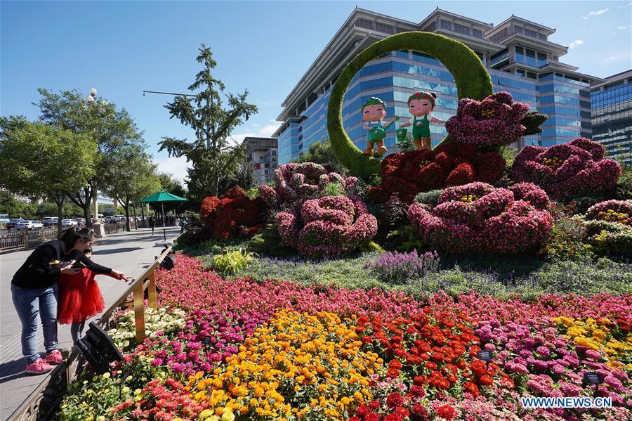 Pedestrians view flower parterres in Beijing, capital of China, Sept. 29, 2018. Beijing is decorated with ornamental flower parterres for the upcoming China\'s National Day. (Xinhua/Ju Huanzong)