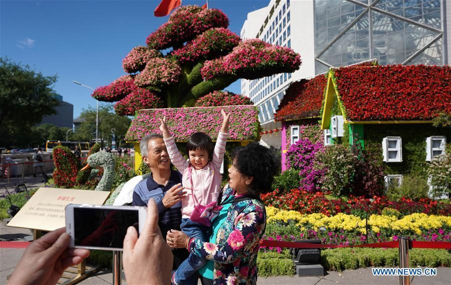 Pedestrians pose for photos with flower parterres in Beijing, capital of China, Sept. 29, 2018. Beijing is decorated with ornamental flower parterres for the upcoming China\'s National Day. (Xinhua/Ju Huanzong)