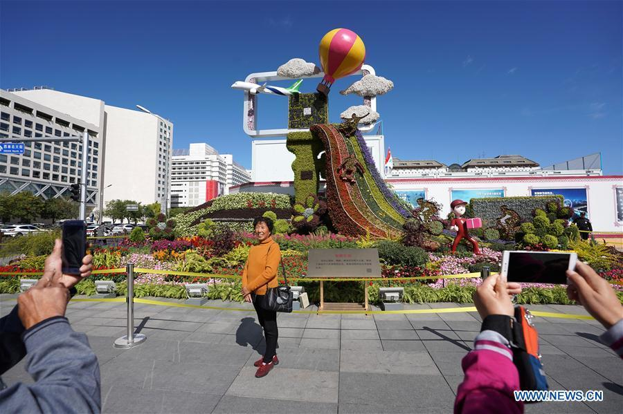 Pedestrians take photos with flower parterres in Beijing, capital of China, Sept. 29, 2018. Beijing is decorated with ornamental flower parterres for the upcoming China\'s National Day. (Xinhua/Ju Huanzong)