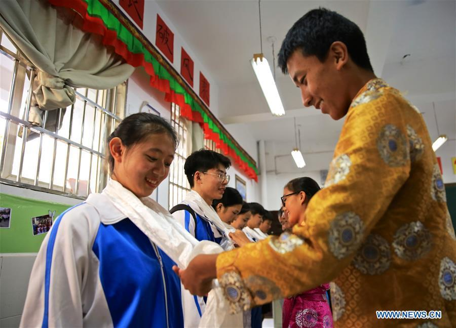 A student of the Tibetan ethnic group (R) offers hada, a ceremonial silk scarf regarded as a token of respect, to local students of the Han ethnic group in Nanchang, capital of east China\'s Jiangxi Province, Sept. 30, 2018. Some 20 students of the Tibetan ethnic group from the No. 17 Middle School celebrated China\'s National Day with local residents and students. China\'s National Day falls on Oct. 1.(Xinhua/Hu Chenhuan)