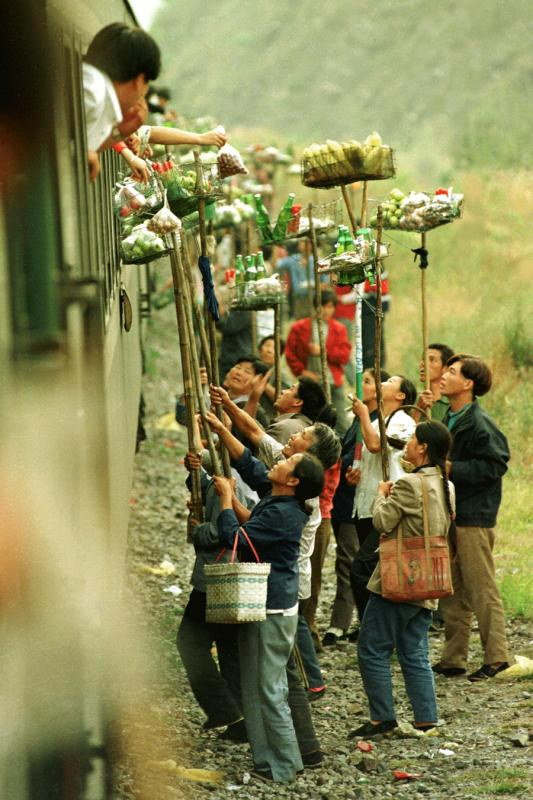 Villagers living near Qiangzilu Railway Station in Miyun district of Beijing, sell local specialties to passengers on a train from Beijing to Qinhuangdao, Hebei province, which stops at the station for five minutes, in October 1996. [ZHOU CHAORONG/FOR CHINA DAILY]