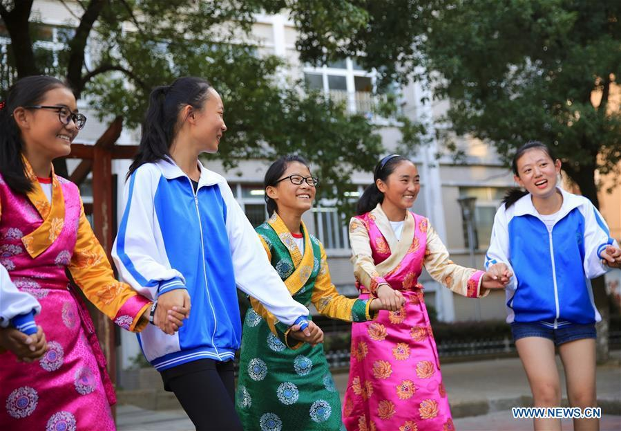 Students of the Tibetan ethnic group dance with peers of the Han ethnic group in Nanchang, capital of east China\'s Jiangxi Province, Sept. 30, 2018. Some 20 students of the Tibetan ethnic group from the No. 17 Middle School celebrated China\'s National Day with local residents and students. China\'s National Day falls on Oct. 1.(Xinhua/Hu Chenhuan)