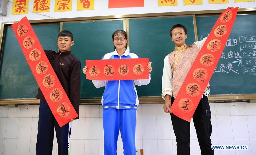A student of the Han ethnic group (C) displays works of calligraphy with peers of the Tibetan ethnic group in Nanchang, capital of east China\'s Jiangxi Province, Sept. 30, 2018. Some 20 students of the Tibetan ethnic group from the No. 17 Middle School celebrated China\'s National Day with local residents and students. China\'s National Day falls on Oct. 1.(Xinhua/Hu Chenhuan)