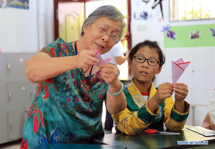 A resident (L) instructs a student of Tibetan ethnic group on paper cutting in Nanchang, capital of east China\'s Jiangxi Province, Sept. 30, 2018. Some 20 students of the Tibetan ethnic group from the No. 17 Middle School celebrated China\'s National Day with local residents and students. China\'s National Day falls on Oct. 1. (Xinhua/Hu Chenhuan)