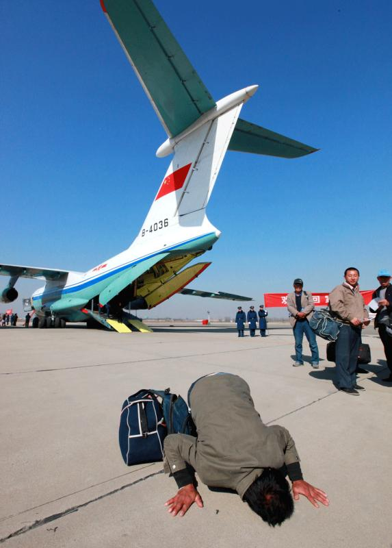 A 41-year-old Sinohydro Corp worker kisses the ground after getting off a plane in Beijing on March 4, 2011. The People\'s Liberation Army Air Force sent four planes to Libya to bring back Chinese nationals after a civil war broke out in the country. A total of 287 Chinese citizens took the planes back to China. It was the first time the PLA Air Force evacuated Chinese nationals from overseas. [SHEN LING/FOR CHINA DAILY]