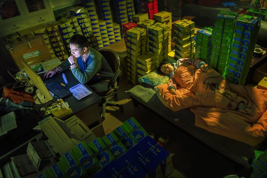 A man manages his e-commerce business at 1 am on Nov 12, 2014, in Wenzhou, Zhejiang province, while his wife sleeps. November 11 is an e-commerce discount day in China. [ZHAO YONG/FOR CHINA DAILY]