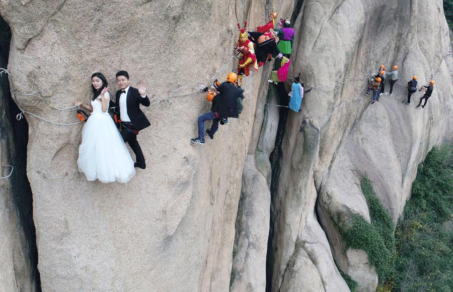 A couple poses for a wedding photo on a cliff at Chaya Mountain Scenic Zone in Zhumadian, Henan province, on Nov 11, 2017. [LU JIAN/FOR CHINA DAILY]