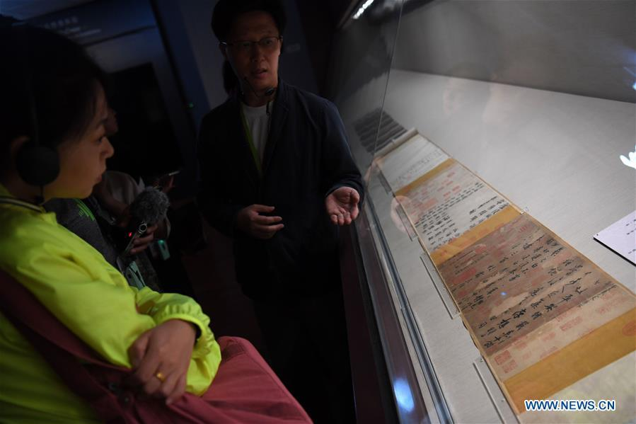 A staff worker introduces a calligraphy work of Wang Xizhi at the palace museum in Taipei, southeast China\'s Taiwan, Oct. 3, 2018. The museum will hold an exhibition under the title of \