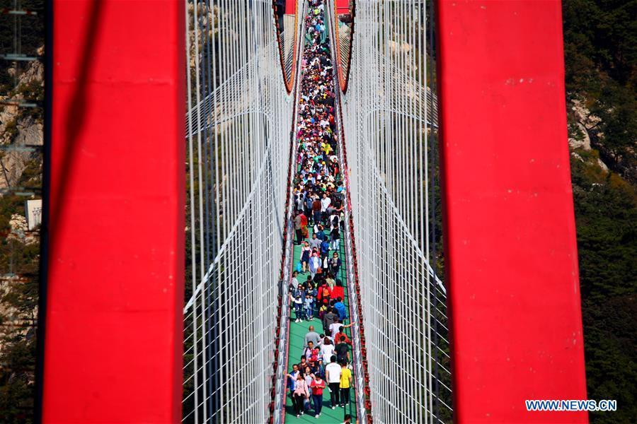Tourists walk on a pedestrian suspension bridge built in the Yimeng mountains in Linyi, east China\'s Shandong Province, Oct. 3, 2018, the third day of the week-long National Day holiday. (Xinhua/Wu Jiquan)