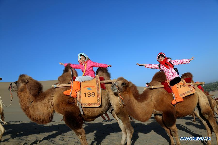 People ride camels at the Crescent Moon Spring scenic spot on the Mingsha Mountain in Dunhuang, northwest China\'s Gansu Province, Oct. 3, 2018, the third day of the week-long National Day holiday. (Xinhua/Zhang Xiaoliang)