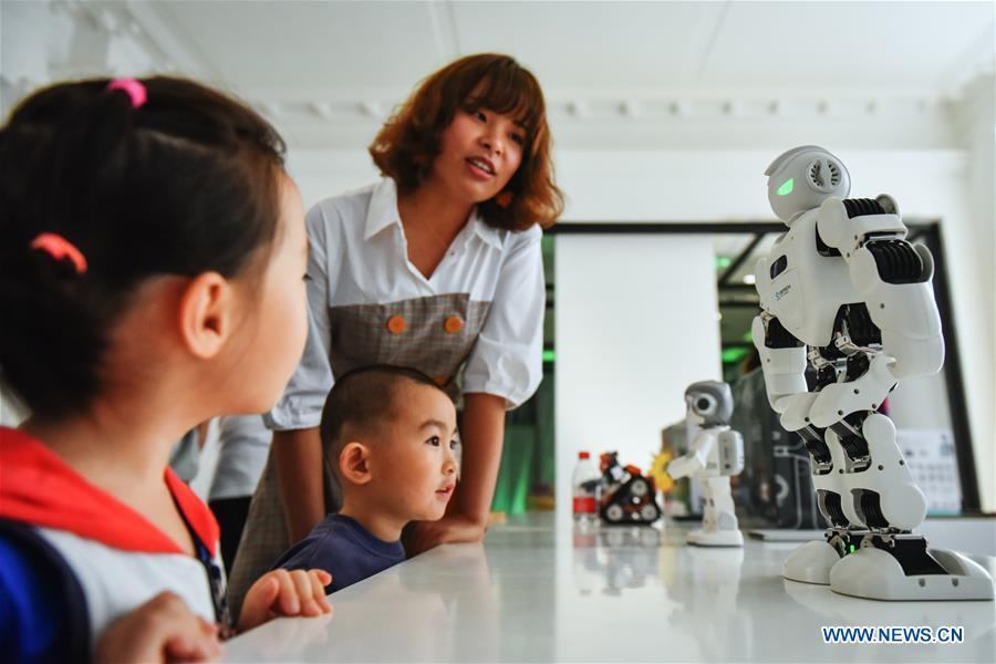Children watch the robots displayed at the Beijing Design Week in Beijing, capital of China, Oct. 4, 2018. The Beijing Design Week, a platform aimed at promoting the concept of a sustainable development of creative and design industry, last from Sept. 22 to Oct. 7. (Xinhua/Li Mangmang)