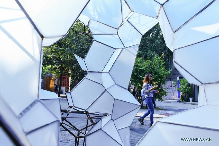 A visitor walks past a decoration art work displayed at the Beijing Design Week in Beijing, capital of China, Oct. 4, 2018. The Beijing Design Week, a platform aimed at promoting the concept of a sustainable development of creative and design industry, last from Sept. 22 to Oct. 7. (Xinhua/Li Mangmang)