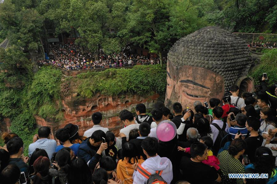 People view the statue of the Leshan Giant Buddha in Leshan City, southwest China\'s Sichuan Province, Oct. 4, 2018. The Leshan Buddha scenic area received about 43,800 visitors on the fourth day of China\'s National Day holiday. (Xinhua/Jiang Hongjing)