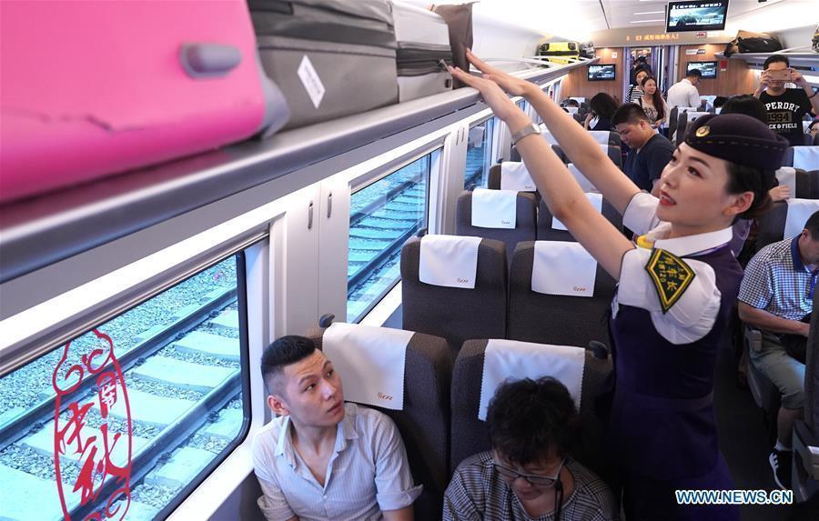 Li Xiaojia, conductor of train G99, arranges the luggage at Hongqiao Railway Station in Shanghai, east China, Sept. 23, 2018. Train G99, the first high-speed train from Shanghai to Hong Kong, left Hongqiao Station on Sept. 23 for Hong Kong West Kowloon Station. (Xinhua/Chen Fei)