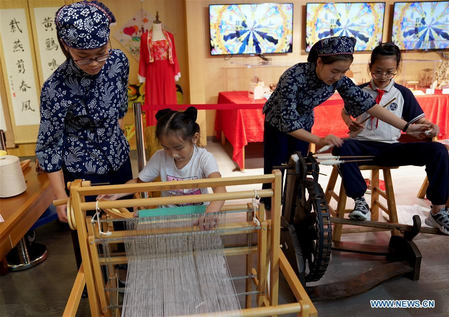 Pupils learn to operate the traditional shuttle loom in Shanghai, east China, Sept. 21, 2018. A series of activities were held in the Shanghai Big World on Sept. 21 to show young people\'s practice of intangible cultural heritages. (Xinhua/Liu Ying)