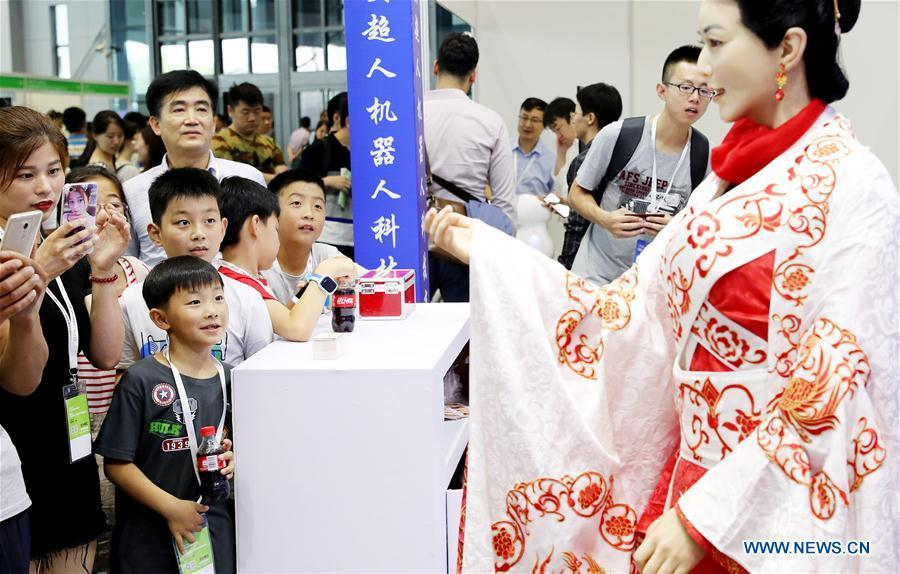 Visitors view a humanoid at China International Robot Show (CiROS) 2018 in east China\'s Shanghai, July 4, 2018. (Xinhua/Fang Zhe)