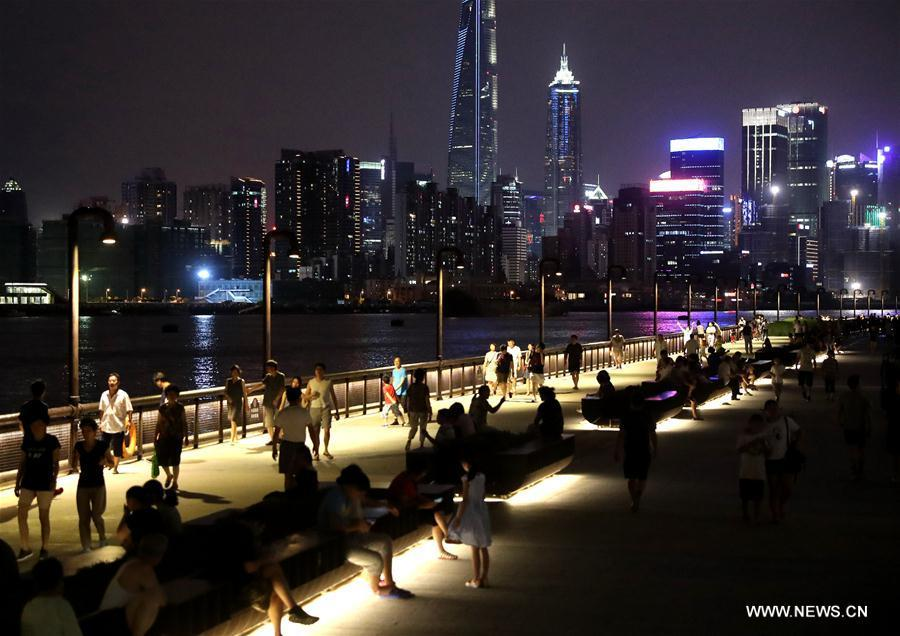 People walk on the riverside avenue by the Huangpu River in Shanghai, east China, July 10, 2017. (Xinhua/Chen Fei)