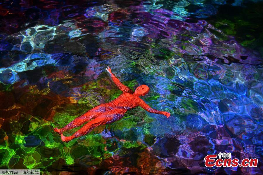 A woman swims in the lighted water of the Hirschengraben indoor swimming pool in Bern during an artistic performance by Swiss visual artist Pipilotti Rist and World Wide Fund for Nature (WWF) Switzerland non-governmental organization to denounce the disappearance of corals due to the warming and the acidification of the ocean on October 7, 2018. (Photo/Agencies)