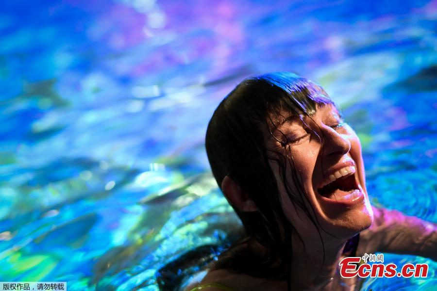 Swiss visual artist Pipilotti Rist laughs as she poses in the lighted water of the Hirschengraben indoor swimming pool during an artistic performance and World Wide Fund for Nature (WWF) Switzerland non-governmental organization to denounce the disappearance of corals due to the warming and the acidification of the ocean on October 7, 2018. (Photo/Agencies)