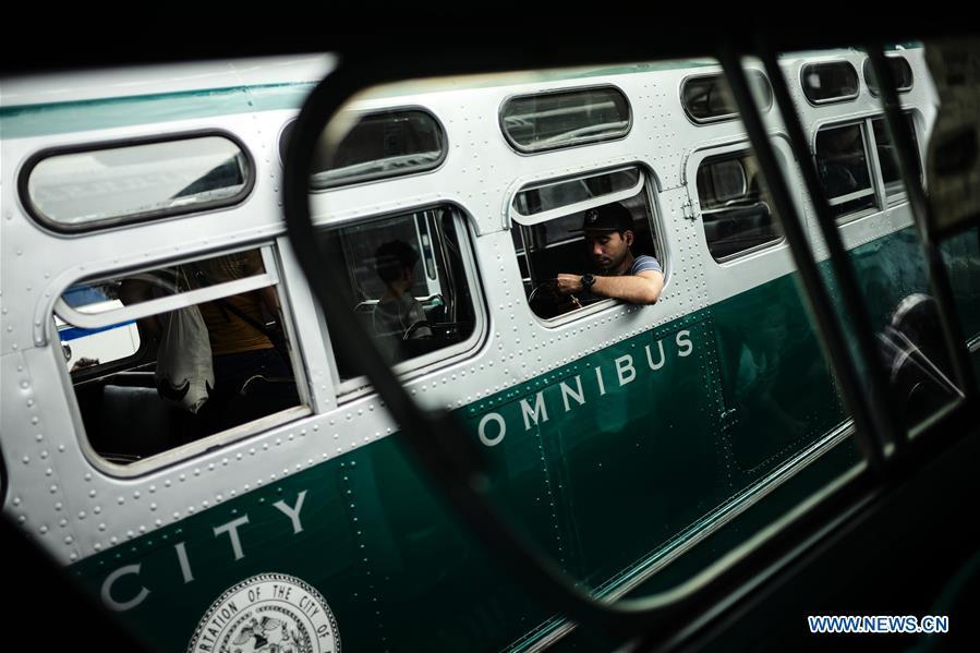 A man sits inside a vintage bus during the 25th Annual Bus Festival in New York, the United States, on Oct. 7, 2018. The New York Transit Museum held its 25th annual bus festival on Sunday. The buses on display represent about 80 years of surface transit history in New York City. The oldest bus at the festival, Bus 1263, is a double-decker bus that was purchased by the Fifth Avenue Bus Company in 1930. (Xinhua/Li Muzi)