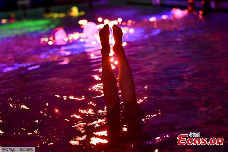 People swim in the lighted water of the Hirschengraben indoor swimming pool in Bern during an artistic performance by Swiss visual artist Pipilotti Rist and World Wide Fund for Nature (WWF) Switzerland non-governmental organization to denounce the disappearance of corals due to the warming and the acidification of the ocean on October 7, 2018.  (Photo/Agencies)