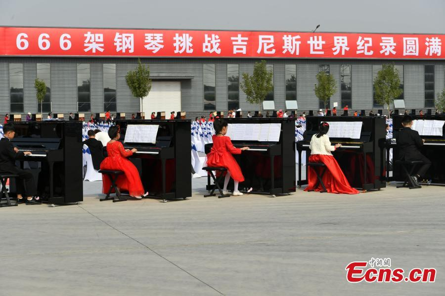 Participants play pianos at the same time in an attempt to set a Guinness World Record for the most pianos played simultaneously at the R?NISCH industry park in Wuqiang County, North China's Hebei Province, Oct. 6, 2018. A total of 666 pianos were played in the challenge. (Photo: China News Service/Zhai Yujia)