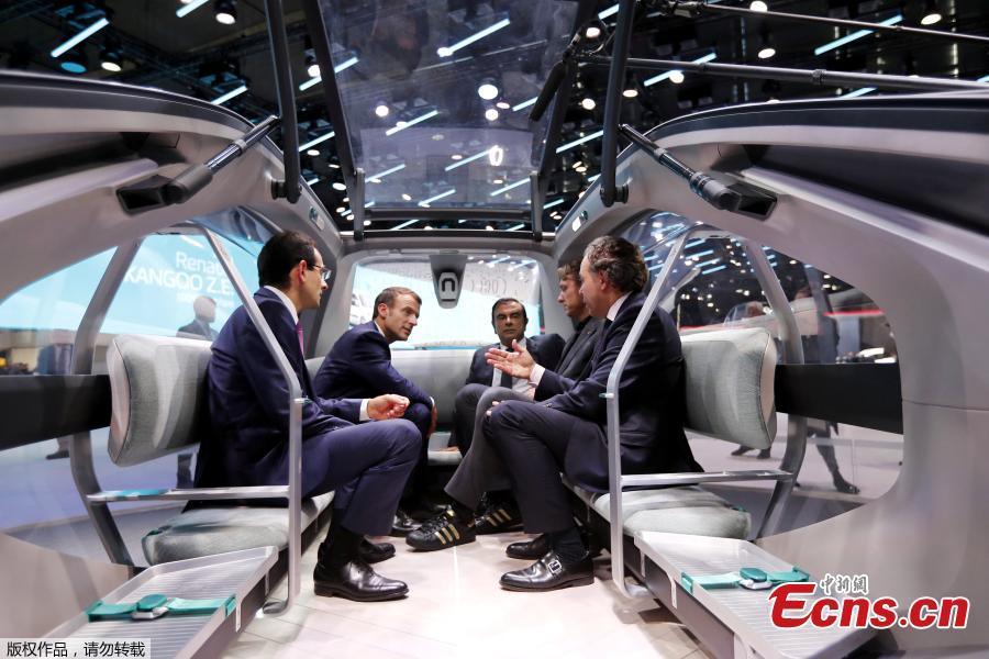 French President Emmanuel Macron, Carlos Ghosn the CEO of French carmaker Renault, and French politician Luc Chatel speak at the the Renault stand during an official visit at the Paris Motor Show in Paris, France October 3, 2018. (Photo/Agencies)