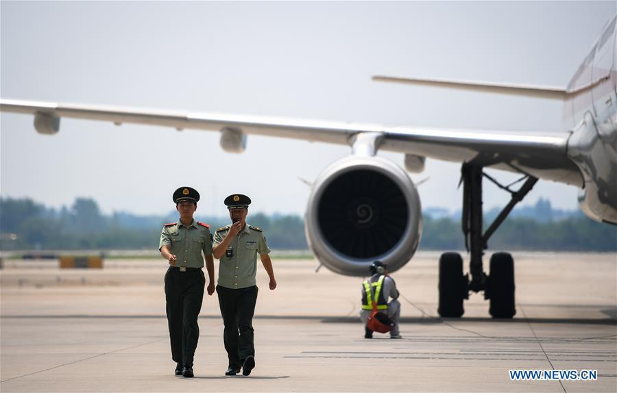 Wang Zhiguo (R) patrols a parking apron of Nanjing Lukou International Airport in Nanjing, capital of east China\'s Jiangsu Province, Aug. 7, 2018. Wang Jicai, who used to be head of the militia post on Kaishan Island in Jiangsu Province, started working on the island in the Yellow Sea with his wife in 1986. He died of sudden illness while on duty in July of 2018 at the age of 58. Wang Zhiguo, son of Wang Jicai, became a frontier defence policeman after his graduation from Nanjing University of Aeronautics and Astronautics in 2013. He had been assigned to many security tasks for major events during 5 years\' working. (Xinhua/Li Xiang)