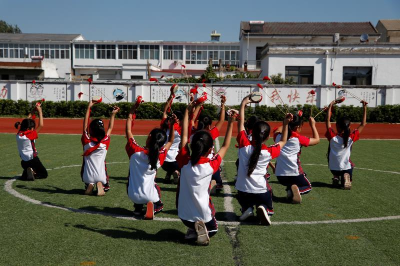 A group of primary school students perform the Fengyang Flower-drum Dance during a break between classes on Sept. 27. Popular in Fengyang county, which governs Xiaogang village, the dance has a history of more than 600 years. (Photo/chinadaily.com.cn)