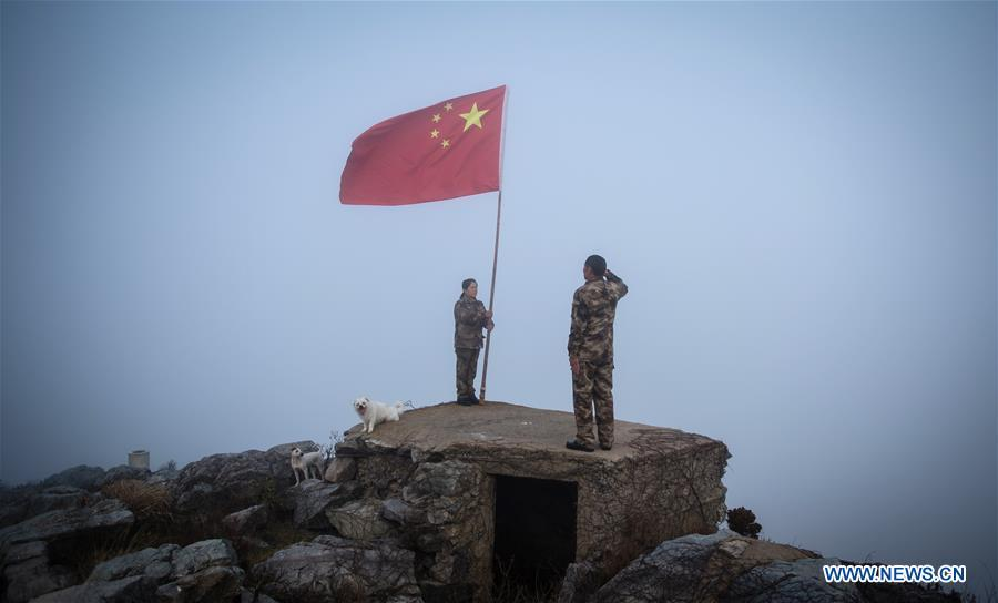 Wang Jicai (R) salutes the national flag on Kaishan Island of Guanyun County, east China\'s Jiangsu Province, Jan. 1, 2017. Wang Jicai, who used to be head of the militia post on Kaishan Island in Jiangsu Province, started working on the island in the Yellow Sea with his wife in 1986. He died of sudden illness while on duty in July of 2018 at the age of 58. Wang Zhiguo, son of Wang Jicai, became a frontier defence policeman after his graduation from Nanjing University of Aeronautics and Astronautics in 2013. He had been assigned to many security tasks for major events during 5 years\' working. (Xinhua/Li Xiang)