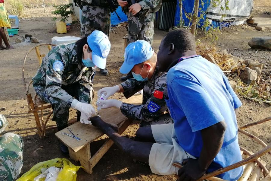 Chinese peacekeepers provide medical care to people in Juba, South Sudan. (Photo/CHINA DAILY)  Growing contribution to UN missions ensures stable development  Loud cheers fill the sweltering air in Juba, capital of South Sudan.  It is Aug. 1, Army Day, when China celebrates the founding of the People\'s Liberation Army in 1927, and soldiers of the Chinese Peacekeeping Infantry Battalion are commemorating the event.  With colleagues cheering wildly on the sidelines, competitors in a relay race involving battalion members pass the baton, heedless of the scorching sun, and the support company eventually wins the day.  For more than a decade, China has been playing a bigger role in protecting global peace. This is the fourth group of infantry soldiers drawn from the 83rd Combined Corps of the PLA.  Under the United Nations Mission in South Sudan, they are assigned to protect local civilians and UN personnel and humanitarian assistance staff members, patrol defense areas, secure the UN compound, enforce a weapon-free zone and escort humanitarian assistance to areas under their jurisdiction.  They also have safely evacuated UN personnel during emergencies. On average, 506 troops have been deployed daily, along with 73 vehicles and hundreds of weapons.  The 700-strong battalion, consisting of infantry and artillery personnel, scouts and engineers, arrived in four groups in November. It is nearing the end of its mission.  \