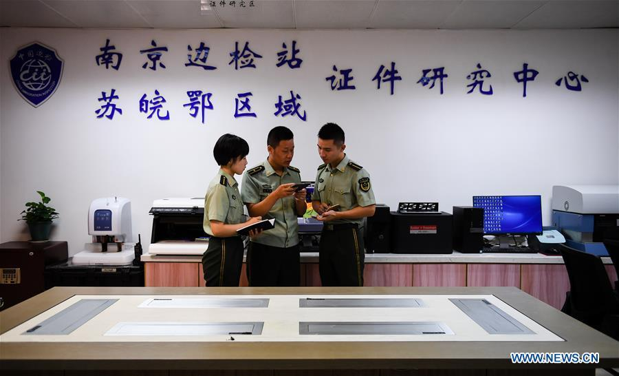 Wang Zhiguo (C) discusses on certificate identification with colleagues at Nanjing Lukou International Airport in Nanjing, capital of east China\'s Jiangsu Province, Aug. 7, 2018. Wang Jicai, who used to be head of the militia post on Kaishan Island in Jiangsu Province, started working on the island in the Yellow Sea with his wife in 1986. He died of sudden illness while on duty in July of 2018 at the age of 58. Wang Zhiguo, son of Wang Jicai, became a frontier defence policeman after his graduation from Nanjing University of Aeronautics and Astronautics in 2013. He had been assigned to many security tasks for major events during 5 years\' working. (Xinhua/Li Xiang)