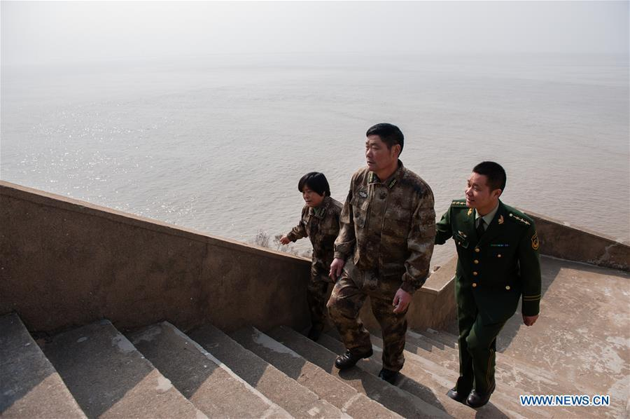 Wang Zhiguo (R) walks with his parents on Kaishan Island of Guanyun County, east China\'s Jiangsu Province, Feb. 13, 2015. Wang Jicai, who used to be head of the militia post on Kaishan Island in Jiangsu Province, started working on the island in the Yellow Sea with his wife in 1986. He died of sudden illness while on duty in July of 2018 at the age of 58. Wang Zhiguo, son of Wang Jicai, became a frontier defence policeman after his graduation from Nanjing University of Aeronautics and Astronautics in 2013. He had been assigned to many security tasks for major events during 5 years\' working. (Xinhua/Li Xiang)