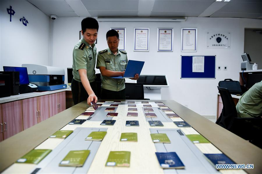 Wang Zhiguo (R) works at an inspection station of Nanjing Lukou International Airport in Nanjing, capital of east China\'s Jiangsu Province, Aug. 7, 2018. Wang Jicai, who used to be head of the militia post on Kaishan Island in Jiangsu Province, started working on the island in the Yellow Sea with his wife in 1986. He died of sudden illness while on duty in July of 2018 at the age of 58. Wang Zhiguo, son of Wang Jicai, became a frontier defence policeman after his graduation from Nanjing University of Aeronautics and Astronautics in 2013. He had been assigned to many security tasks for major events during 5 years\' working. (Xinhua/Li Xiang)