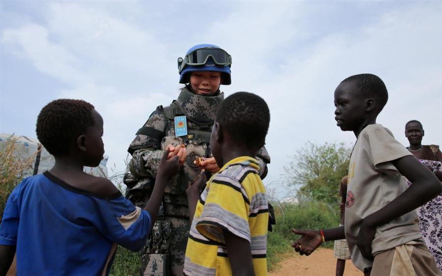 Jia Xiaochen, a Chinese peacekeeper in the infantry squad shares candy with children in Juba. (Photo/Xinhua)  Growing stature  Joining the battalion at its camp during the Army Day celebrations, the deputy head of UNMISS, Moustapha Soumare, said the presence of Chinese peacekeepers was reassuring, given the complex situation and volatility in South Sudan.  \