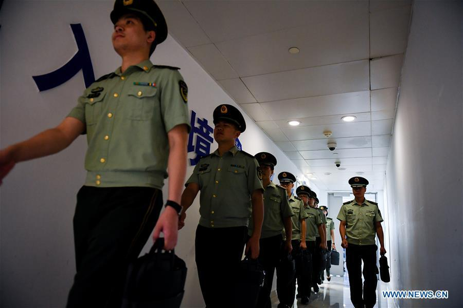 Wang Zhiguo (1st R) perpares to work at Nanjing Lukou International Airport in Nanjing, capital of east China\'s Jiangsu Province, Aug. 7, 2018. Wang Jicai, who used to be head of the militia post on Kaishan Island in Jiangsu Province, started working on the island in the Yellow Sea with his wife in 1986. He died of sudden illness while on duty in July of 2018 at the age of 58. Wang Zhiguo, son of Wang Jicai, became a frontier defence policeman after his graduation from Nanjing University of Aeronautics and Astronautics in 2013. He had been assigned to many security tasks for major events during 5 years\' working. (Xinhua/Li Xiang)