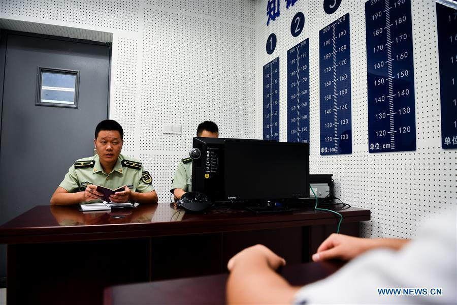 Wang Zhiguo (L) questions a suspect at an inspection station of Nanjing Lukou International Airport in Nanjing, capital of east China\'s Jiangsu Province, Aug. 7, 2018. Wang Jicai, who used to be head of the militia post on Kaishan Island in Jiangsu Province, started working on the island in the Yellow Sea with his wife in 1986. He died of sudden illness while on duty in July of 2018 at the age of 58. Wang Zhiguo, son of Wang Jicai, became a frontier defence policeman after his graduation from Nanjing University of Aeronautics and Astronautics in 2013. He had been assigned to many security tasks for major events during 5 years\' working. (Xinhua/Li Xiang)