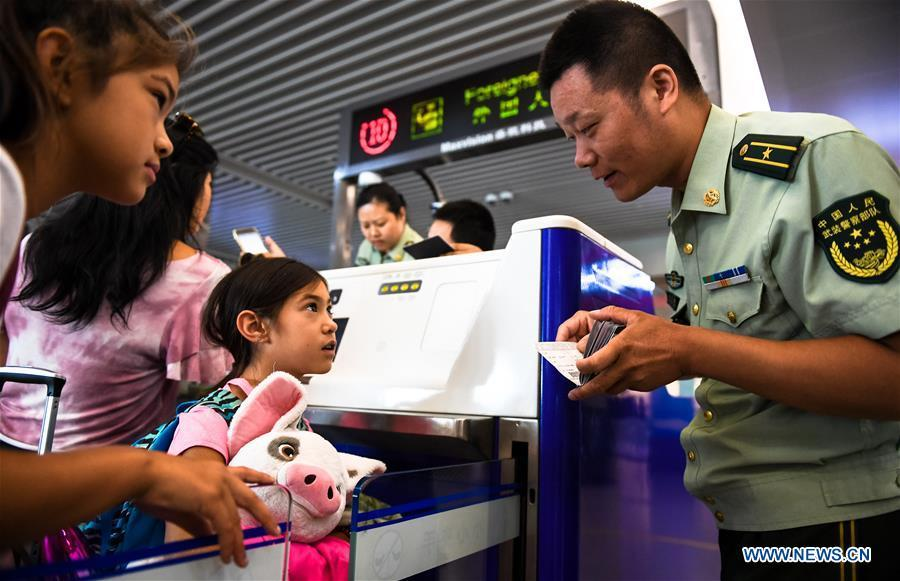 Wang Zhiguo (R) checks passengers\' identity certificates at Nanjing Lukou International Airport in Nanjing, capital of east China\'s Jiangsu Province, Aug. 7, 2018. Wang Jicai, who used to be head of the militia post on Kaishan Island in Jiangsu Province, started working on the island in the Yellow Sea with his wife in 1986. He died of sudden illness while on duty in July of 2018 at the age of 58. Wang Zhiguo, son of Wang Jicai, became a frontier defence policeman after his graduation from Nanjing University of Aeronautics and Astronautics in 2013. He had been assigned to many security tasks for major events during 5 years\' working. (Xinhua/Li Xiang)